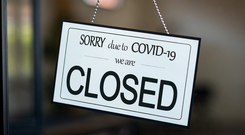 "White sign hanging in window that reads ""SORRY due to COVID-19 we are CLOSED."""