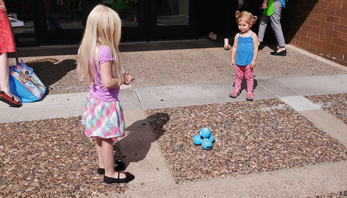 Girls playing with Dash the robot