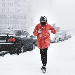 Man walking on snowy road with headphones