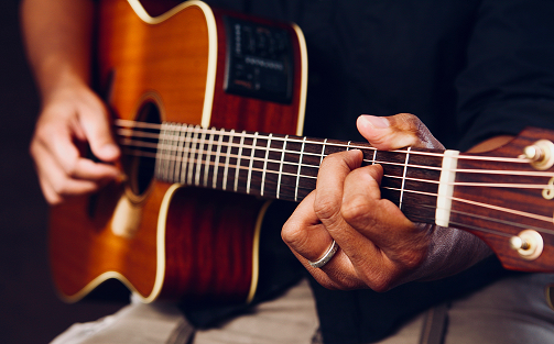 Close-up of someone playing the acoustic guitar.