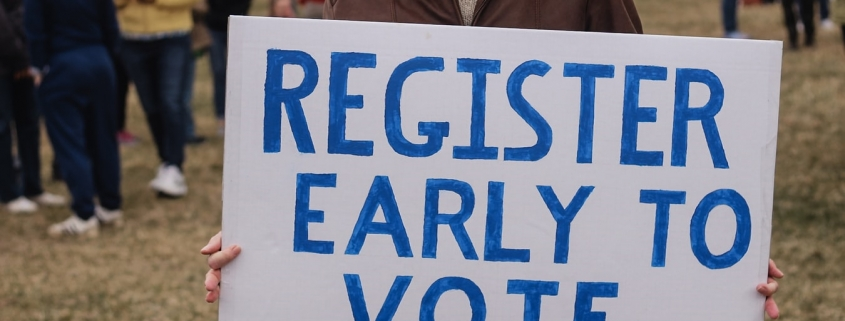 Man holding a sign that reads register early to vote.