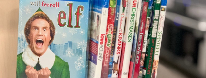 Several Christmas movies on a book shelf with the movie, Elf, faced out.