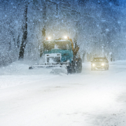Image shows a city snowplow plowing a snowy street.
