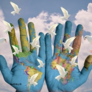 World map on two hands with doves flying into a blue sky with fluffy white clouds